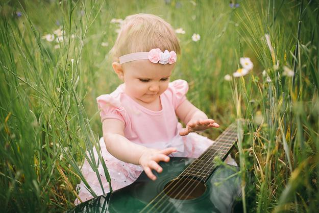 Fotograf für Babyfotos in Bamberg fotografiert Baby in der Natur mit Gitarre